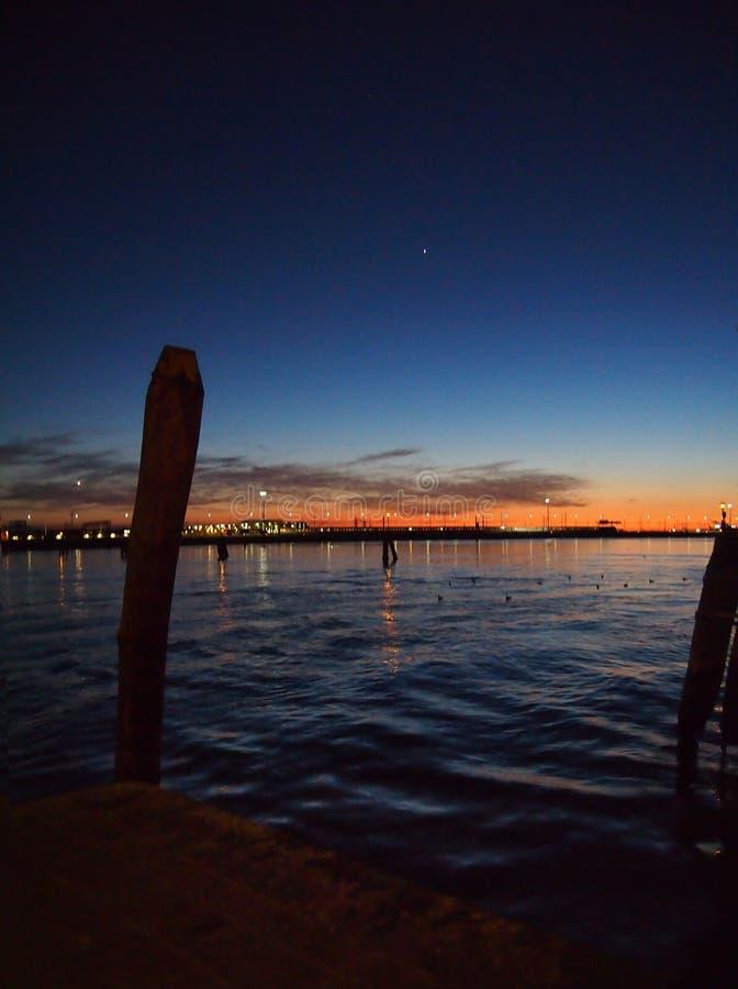 在威尼斯盐水湖的夜有在剪影在海和有启发性日落天空反映的城市光的停泊岗位的 免版税库存照片