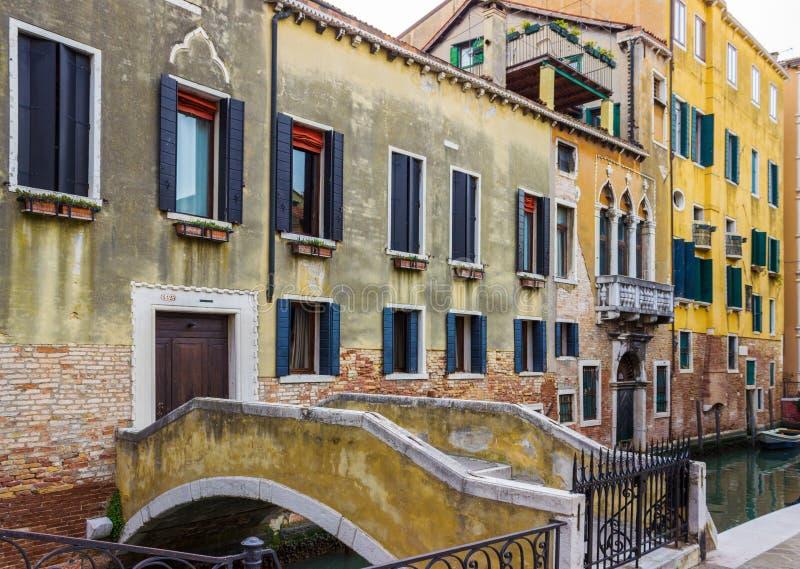 在威尼斯,意大利跨接导致横跨运河的房子 免版税库存照片
