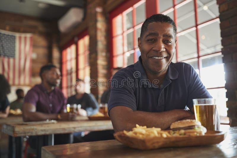 在娱乐酒吧吃汉堡和油炸物的人画象  免版税库存照片