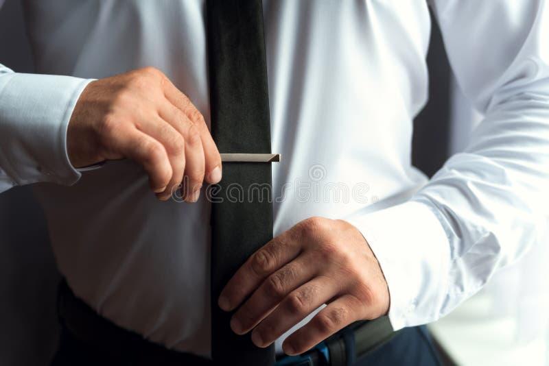 在婚礼前的早晨新郎,投入领带 免版税库存图片