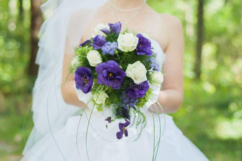 在婚礼在阳光下公园以后的新娘拿着美丽的花束 免版税库存照片
