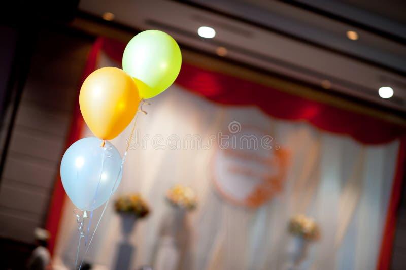 在婚礼大厅里装饰的三个淡色气球 免版税库存照片