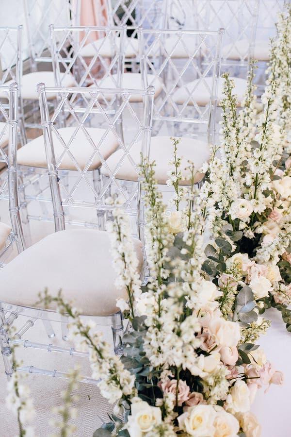 在婚礼的一定数量的透明设计师椅子沿着玫瑰和毛茛的美好的植物布置 图库摄影