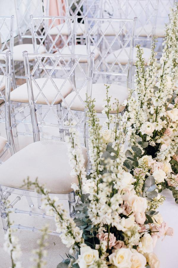 在婚礼的一定数量的透明设计师椅子沿着玫瑰和毛茛的美好的植物布置 库存图片