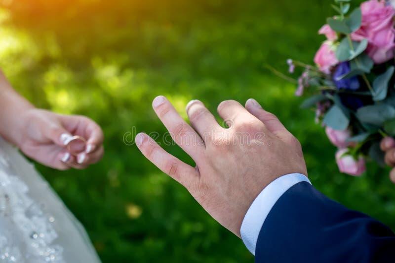 在婚礼的交换结婚戒指,手特写镜头 免版税库存图片