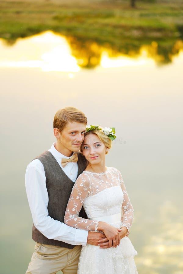 在婚礼的夫妇盛装反对湖的背景在日落、新娘和新郎 库存照片