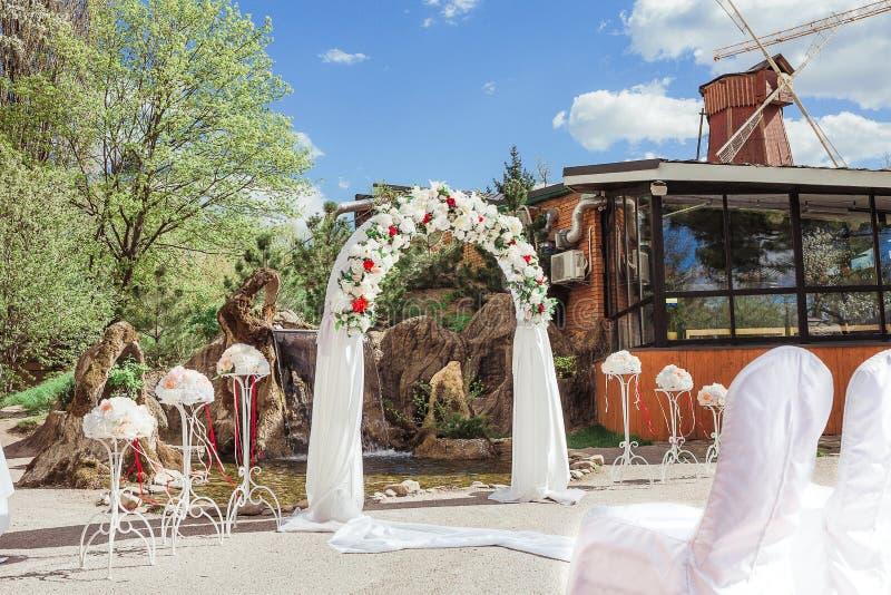 在婚礼的婚礼曲拱在豪华庭院里 库存照片