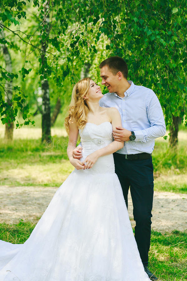 在婚礼礼服的结婚的爱恋的行家在绿色领域的夫妇和衣服在日落的一个森林里 愉快新娘的新郎 库存照片