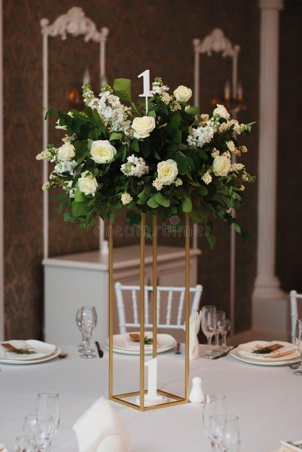 在婚礼表金黄支持的美好的白色和绿色花装饰安排 婚姻的新娘花装饰 库存图片