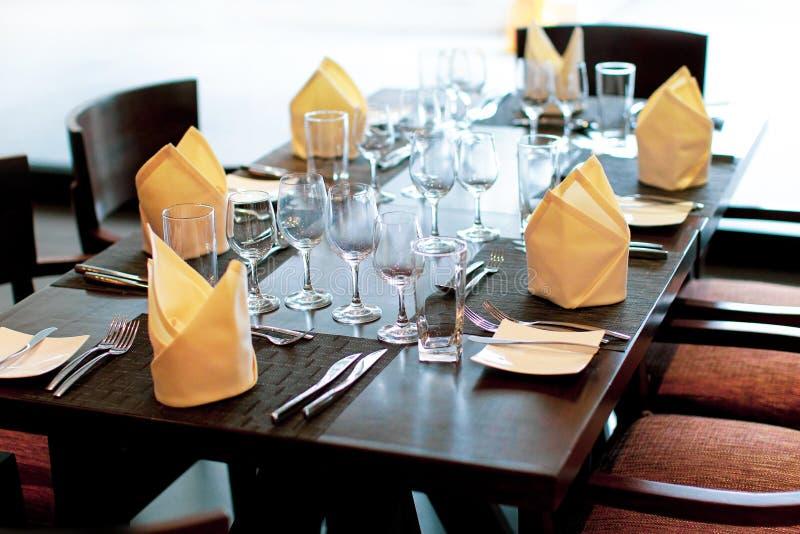 在婚礼装饰的表设置,服务的桌在有酒杯的餐馆和利器 表为婚姻的宴会服务 免版税库存照片