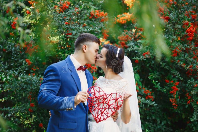 在婚纱和衣服的已婚爱恋的行家夫妇 免版税库存图片