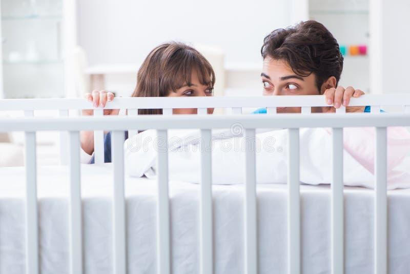 在婴孩床轻便小床的愉快的年轻家庭 免版税图库摄影