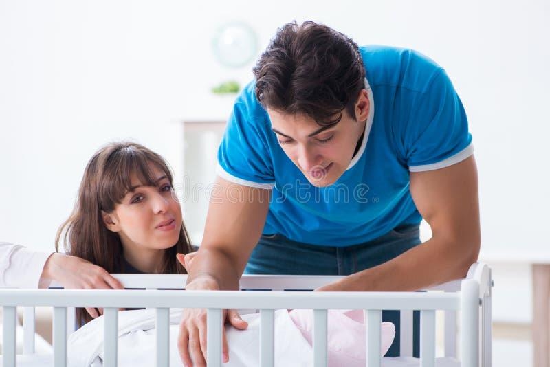 在婴孩床轻便小床的愉快的年轻家庭 库存照片