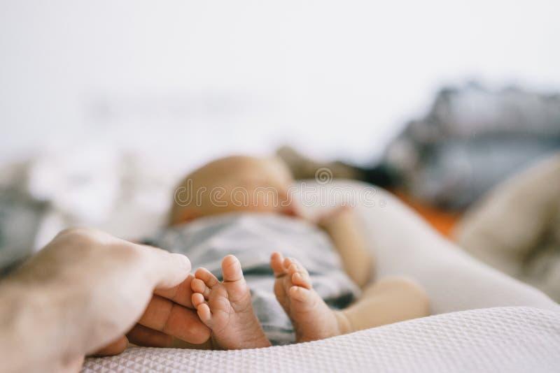 在婴孩茧和他的父亲的手的新出生的婴孩的脚被削减和轻轻地关心 免版税库存照片
