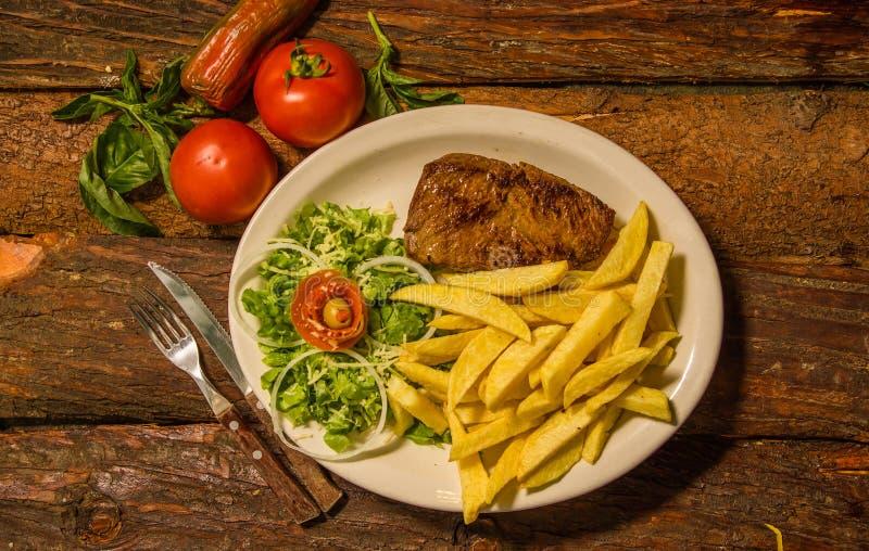 在媒介上看法烤了牛排Ribeye用在白色板材供食的法国土豆,蕃茄,红萝卜,叉子和 免版税库存图片