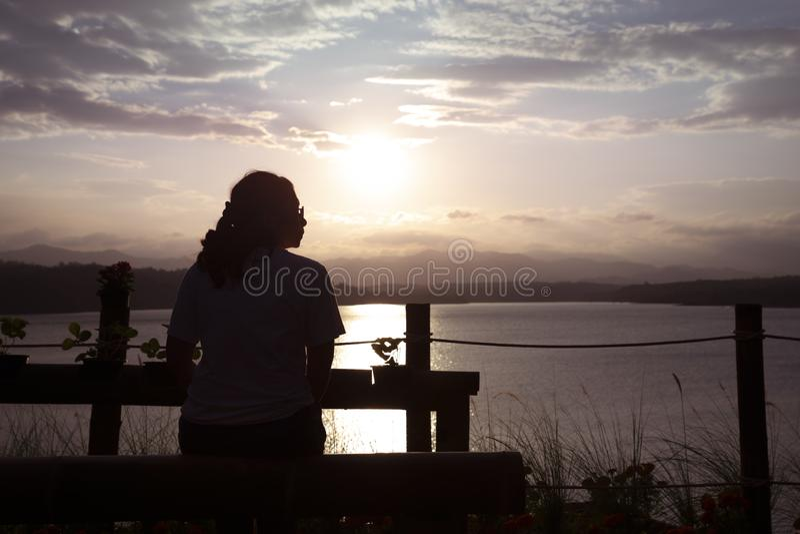 在孑然的逗留 坐的妇女观看阳光在晚上 免版税库存照片