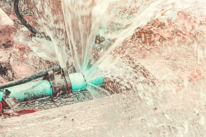 在孔垄沟的破裂的导管在路旁和水行动小野鸭和橙色口气 免版税库存照片