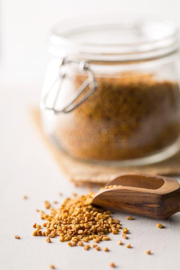 在存贮玻璃瓶子的干,未加工的胡芦巴籽在白色木桌背景与wodden瓢 库存照片
