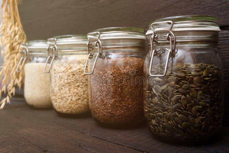 在存贮瓶子的各种各样的种子在餐具室,黑暗的木背景 聪明的厨房组织 库存照片
