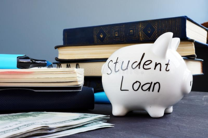 在存钱罐和金钱写的学生贷款 免版税图库摄影