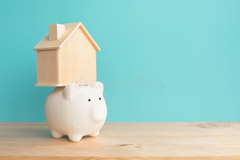 在存钱罐的家庭房子大模型木桌背景的 储款金钱和财政概念 对未来的目标 免版税图库摄影
