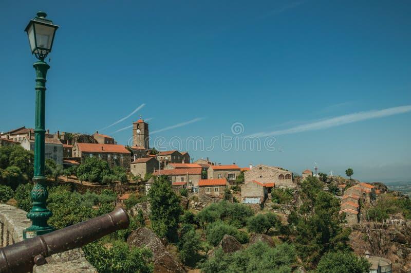 在孟山都村庄前面的老铁大炮在小山顶部 库存图片