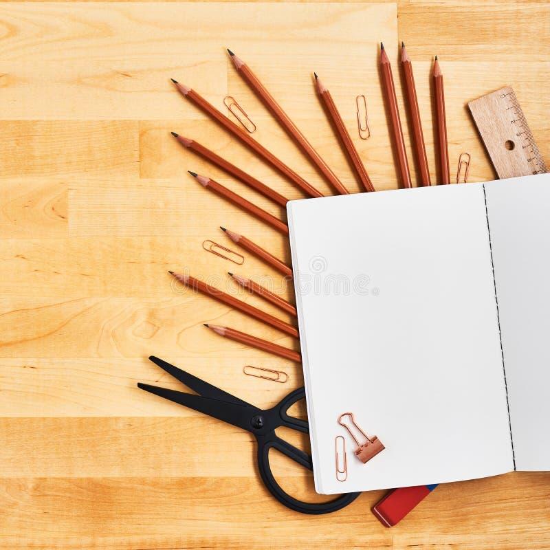 在学校和办公用品的空白的笔记薄在黄色木桌上 免版税库存图片