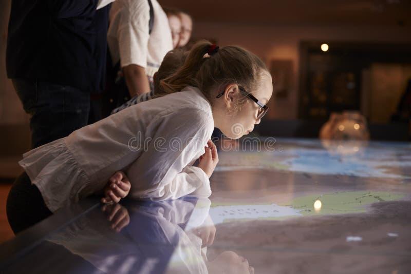 在学校实地考察的学生到看地图的博物馆 免版税库存图片