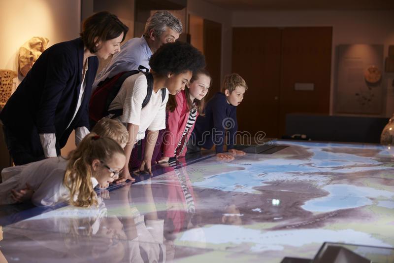 在学校实地考察的学生到看地图的博物馆 免版税库存照片