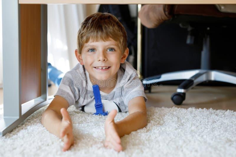 在学校桌下的美丽的微笑的小男孩画象 看照相机的愉快的孩子 有白肤金发的可爱的孩子 免版税库存照片