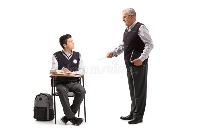 在学校椅子安装的少年学生看他的professo 免版税库存照片