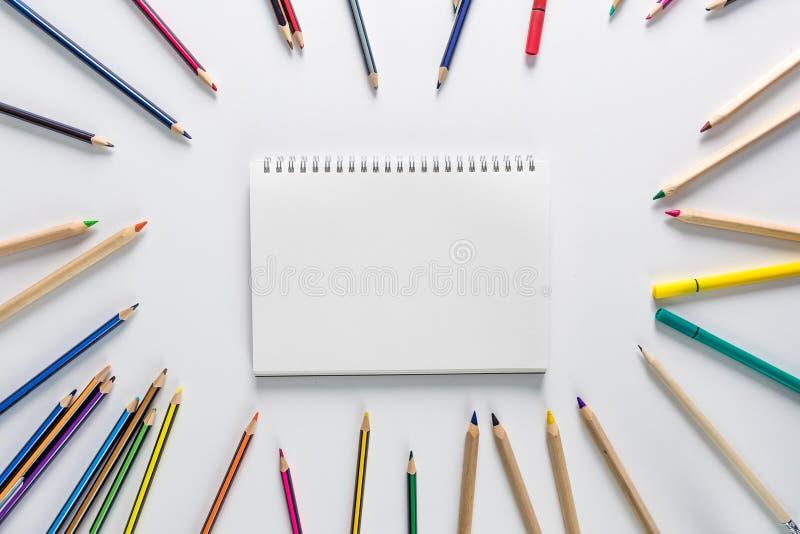 在学校用品的顶视图,在圈子安置的色的铅笔在与空白的著作的白色背景在中间 库存照片