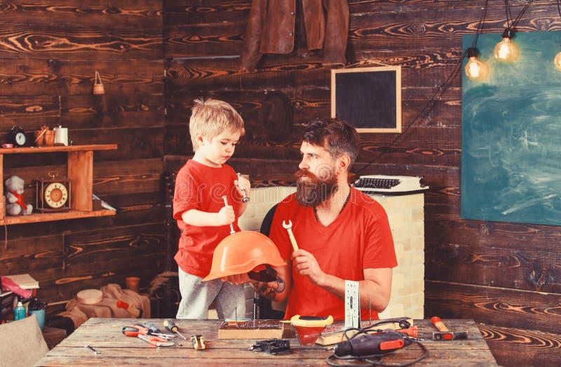 在学校车间生,有胡子的父母举行盔甲教的儿子安全 男孩、儿童快乐的举行螺栓或者螺丝 免版税图库摄影
