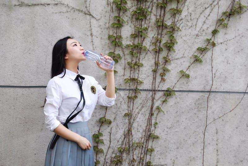 在学校饮用水的愉快的亚洲中国俏丽的女孩穿戴学生衣服本质上在春天 免版税库存图片
