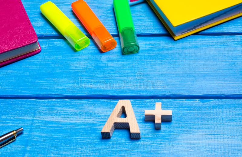 在学生` s书桌上的木信件A加号 在一张蓝色木桌上的学校用品 高中评估的概念,好 库存照片