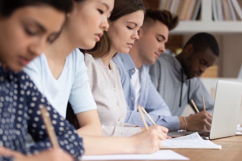 在学院演讲期间,多文化学生做笔记 免版税库存图片