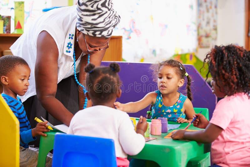 在学龄前类的老师帮助的孩子 免版税库存照片