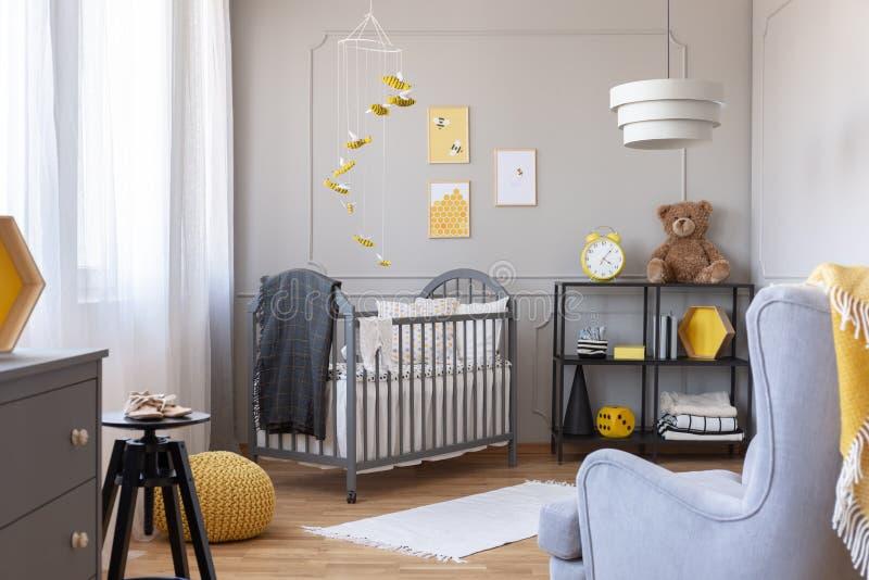 在孩子室内部的蜂装饰与小儿床、扶手椅子和玩具熊 免版税库存图片
