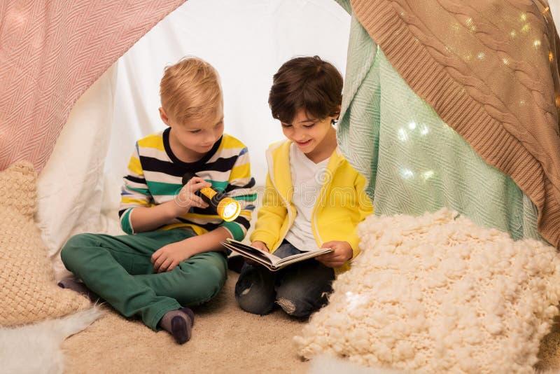 在孩子帐篷的愉快的男孩阅读书在家 库存照片