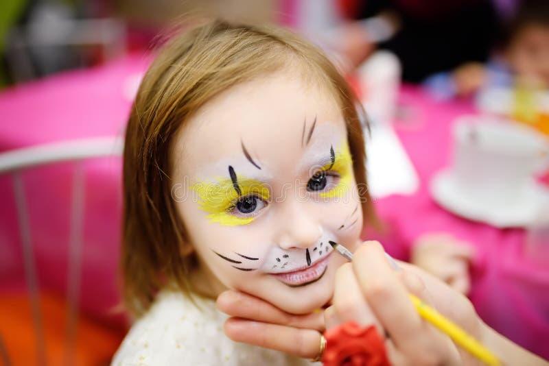 在孩子生日聚会期间,面对逗人喜爱的小女孩的绘画 库存照片