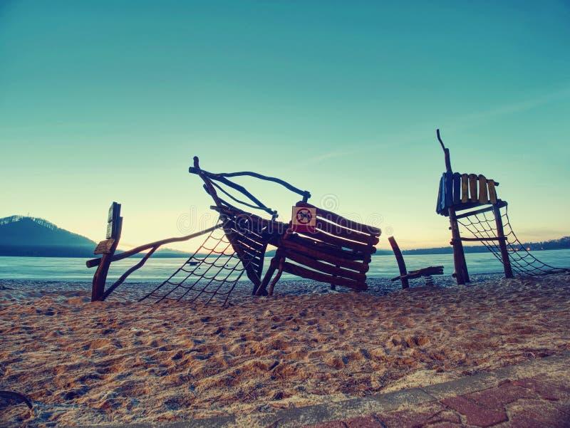 在孩子的沙滩制造的木船 库存照片