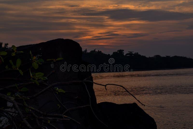 在它上的橙色天空与令人敬畏的在安静的太阳金黄反射挥动作为背景 在海滩的惊人的夏天日落视图 免版税库存照片