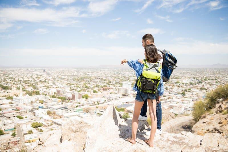 在它上面山享受谷视图的旅客夫妇  免版税图库摄影