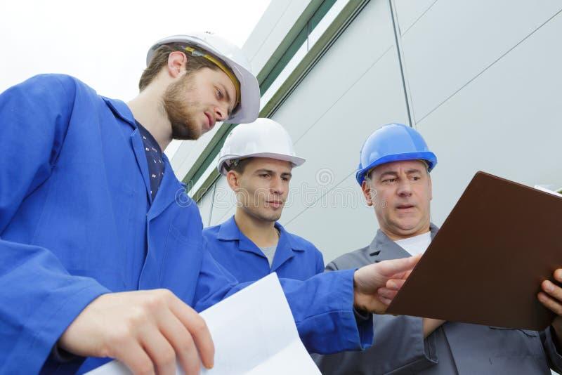 在安全帽的小组建造者有剪贴板的 免版税库存图片