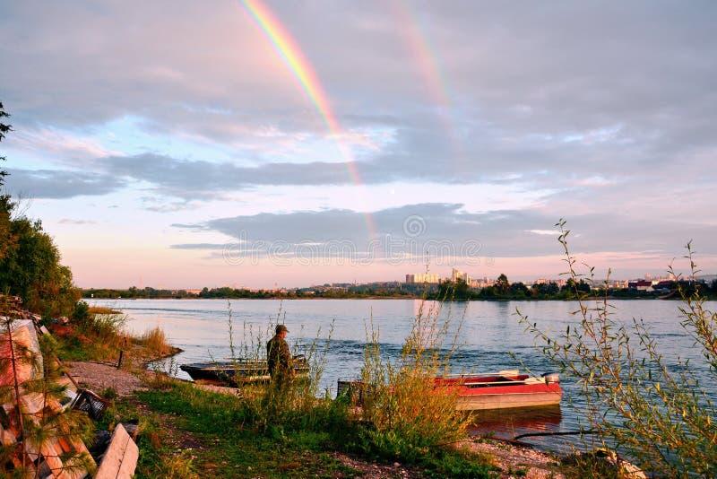 在安加拉河的河岸的一个晚上在伊尔库次克市 从河的海岛的看法 明亮的白色云彩和rainb 库存图片
