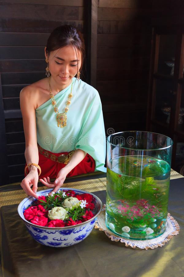 在安排花碗的葡萄酒减速火箭的传统泰国服装的年轻美好的泰国亚洲妇女选矿 文化的泰国和 免版税库存照片