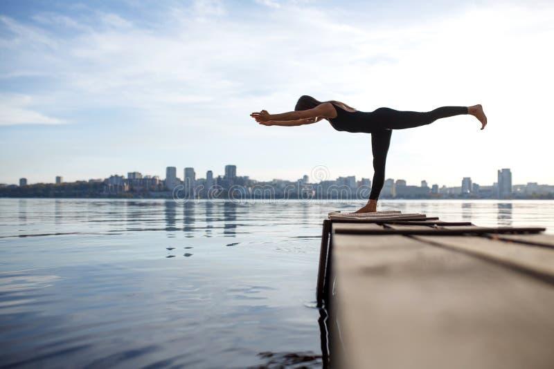 在安静的木码头的年轻女人实践的瑜伽锻炼有城市背景 体育和休闲在城市仓促 图库摄影