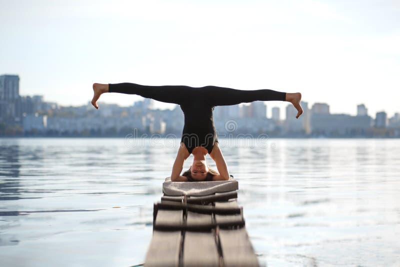 在安静的木码头的年轻女人实践的瑜伽锻炼有城市背景 体育和休闲在城市仓促 免版税图库摄影
