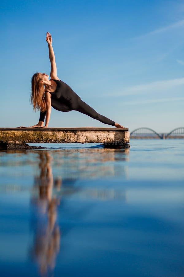 在安静的木码头的年轻女人实践的瑜伽锻炼有城市背景 体育和休闲在城市仓促 库存图片