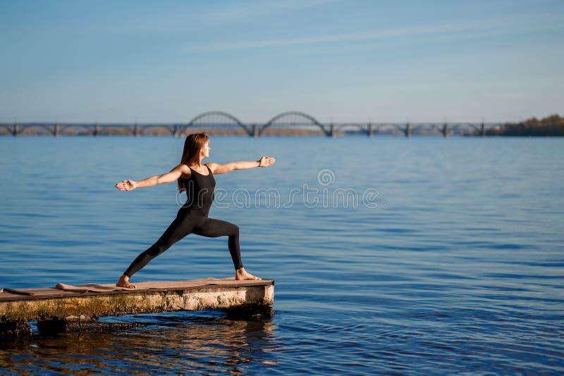 在安静的木码头的年轻女人实践的瑜伽锻炼有城市背景 体育和休闲在城市仓促 免版税库存照片